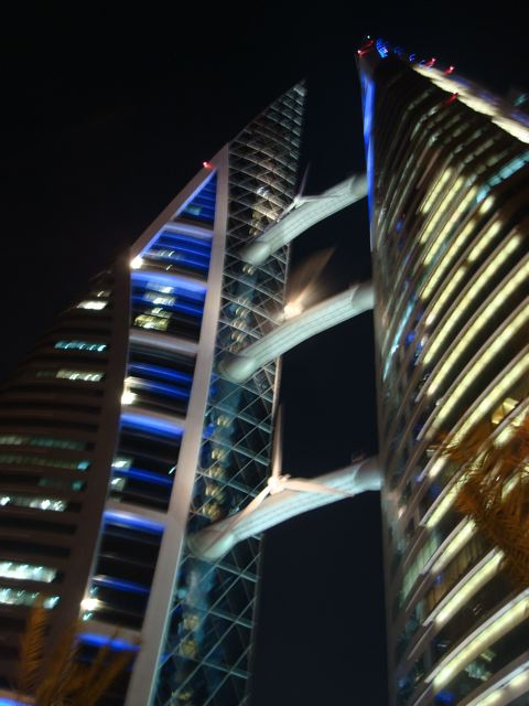 Bahrain's World Trade Centre (at night, with one wind turbine spinning)