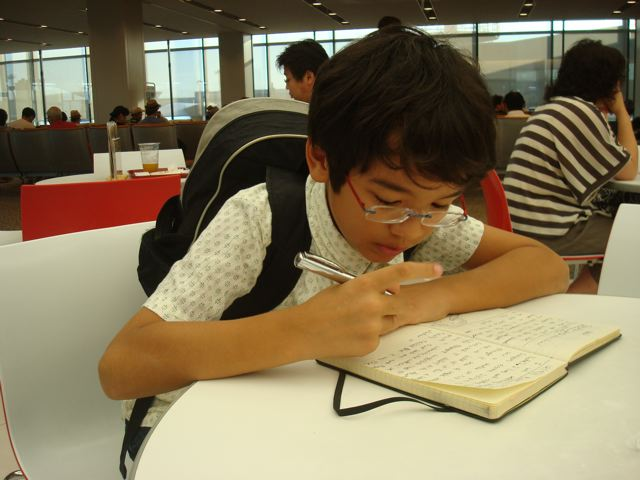 Zen doing homework in Narita airport, en route to Toronto.