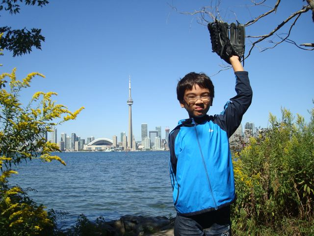 Playing baseball on Toronto Island, with skyline in the background