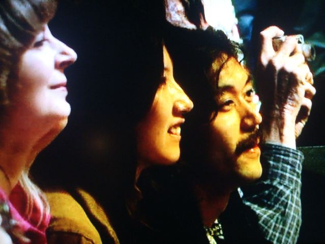 Cute Asian (Japanese?) hippy couple awed to be in front row of Cream reunion concert
